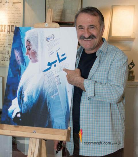 مهران رجبی در کنار پوستر فیلم تابو